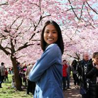A former student smiling surrounded by cherry blossom trees