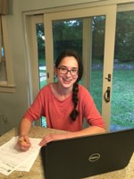 Photo of former student completing work at her kitchen table with her laptop and a big smile on her face